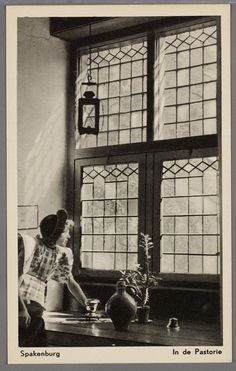 Spakenburg. In de Pastorie. 1920-1940. Vrouw in klederdracht in een interieur, half zittend op de vensterbank voor een glas-in-lood raam. #Utrecht #Spakenburg
