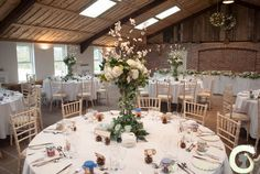 Rustic table centrepiece of roses, hydrangea and blossom with trailing ivy and pine cones