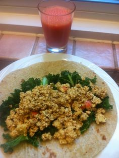 W:l: curry peanut tofu salad w almonds and chopped apple, massaged kale inside of a while grain tortilla; carrot juice