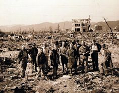 Atomic Bomb Damage to Hiroshima, as seen by USS Appalachian (AGC-1). Officers of USS Appalachian (AGC-1) at bomb damaged Hiroshima. Photographed by PhoM3/C George Almarez. Photographed received October 26, 1945. U.S. Navy photograph, now in the collections of the National Archives.