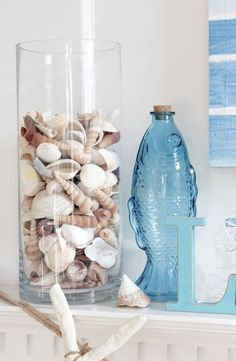 Sail Away Summer mantel with fish bottle and shells in glass container Sail Away Summer mantel with fish bottle and shells in glass container Beach Cottage Style, Beach House Decor, Coastal Style, Coastal Decor, Home Decor, Summer Mantel, Beach Mantle, Beach Bathrooms, Decoration Table