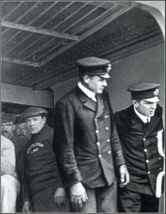 """Only known photograph aboard Titanic and also last known photograph. Pictured alongside Lightoller, as they prepare to close the gangway before depature from Queenstown, Ireland on April 11th, 1912. It is also the last known photograph of a Titanic officer on duty."""
