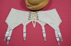 Aufwendig in Handarbeit gefertigter Strapsgürtel aus cremefarbener bestickter Seide . Der Gürtel ist unterfüttert mit haufreundlicher Baumwolle. Strapsgürtel mit 6 verstellbaren Metallstrumpfhaltern, somit kein verrutschen der Nylons mehr. Der Gürtel wird vorn mit Bügelösen gebunden. Sehr angenehm zu tragen und formt eine schöne weibliche Taille.  Ideal als Hochzeits-Dessous. Feinste Handarbeit zum erschwinglichen Preis.