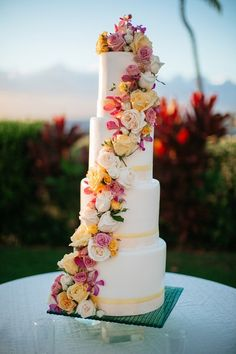 Destination wedding cake idea - tall, four-tier, fondant-frosted wedding cake with pink, orange + white flowers  {Chris J Evans Photography}