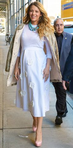 Blake Lively wearing a white knit over an optic white daisy-appliquéd midi-length skirt, both by Michael Kors, with vibrant turquoise beaded strands, blush-pink pumps, and a boucle coat draped over her shoulders.