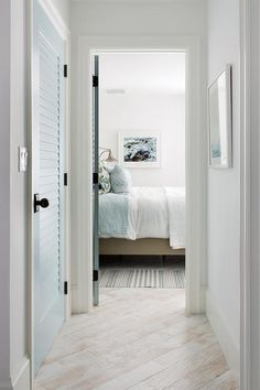 white washed wood floors lead past a blue louvered closet door to a bedroom fitted with