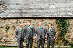 Groomsmen wear a 3 piece grey suit with green tie - Image by The Lou's - Fairytale Donna Lee bridal gown with green bridesmaid dresses for an outdoor ceremony in Cornwall with rustic marquee reception, a scone wedding cake tower & garden games.