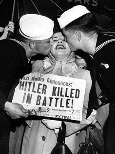 """Sailors Bob Nethery, left, of Powell, Wyo., and Bob Wickford of Patterson, Calif., celebrate the newspaper headline """"Hitler Killed in Battle!"""" by planting kisses on a woman walking past the newstand in New York City, May 1, 1945."""