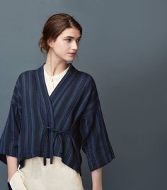 Kimono wrap-top in a soft, light, darkly striped cotton double cloth with 4% wool. Yarn-dyed stripe. Dropped shoulders and wide, below elbow-length sleeves. Fastening at the front with a tie at each side.
