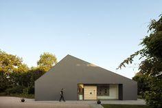 La nuova casa è stata progettata con l'intento di mantenere l'equilibrio volumetrico tra gli edifici esistenti sul lato ovest del cortile: le proporzioni della facciata, le altezze e i materiali riprendono quelli dell'edificio di fronte.