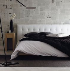 love the white tufted headboard against a newspaper wall
