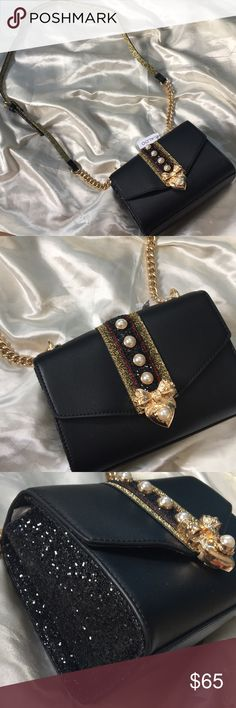 """NWT ALDO Lebovit Black Crossbody Bag BRAND NEW with tag ALDO Lebovit Black Cross body bag! This stunning bag is matte black in color, is embellished front with red, black and gold glitter, pearls and a golden bow. Both sides have black glitter on it and the strap has a golden chain and golden glitter on the inside. Strap is adjustable and not detachable. Interior has one open pocket. Has enough space for a phone, a small wallet and small items. Measurement is about 5"""" X 7"""". Get her now❤️…"""