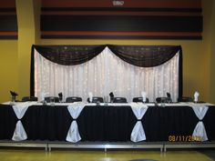 20'Wx8'H drapery & lights backdrop w/black chiffon draping/black tableskirts/white table runners tied w/black sash on front of head table