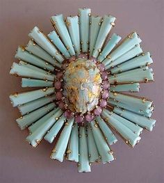 A vintage sunburst brooch made from an oval cabochon, pink rounds, and light turquoise faceted keystone rays. #VintageJewelry