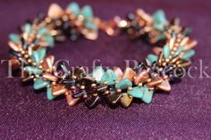 Warm tones of brown, copper, turquoise, and purple make up this beautiful spiral bracelet. Bracelet is made using Czech mates two hole triangle beads and finished with a copper lobster claw clasp. Pho