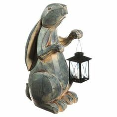 """Carved rabbit-shaped garden statuette with a lantern.  Product: Garden statuetteConstruction Material: Polystone, metal and glassColor: Washed greenFeatures: Includes lanternAccommodates: (1) LED light - includedDimensions: 13.18"""" H x 11"""" W x 6.1"""" D"""