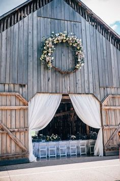 The Barn at Cedar Grove is a rustic Kentucky barn venue - draped and adorned with a floral wreath for a gorgeous barn wedding. Photographer: Anekdota Studio Floral Design: Best of Flowers