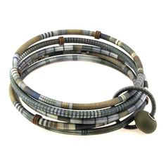 """SHARON MacLEOD.  Design inspired by an Asante textile pattern from Africa.  """"Each bracelet is handmade to order and starts with my own graphic art that I print on thin paper, meticulously laminate to various sizes of small tubing, and assemble with a variety of materials, including polymer clay, glass, metal, rubber and plastic. Because of the nature of the process, no two are exactly alike."""""""