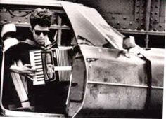 Tom Waits, with accordion, in car.