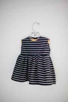 A mini version of the women's dress.   Black with white stripes.  Sleeveless. Zipper closure in the back.     Please include chest measurement and length from shoulder to knee to ensure an accurate fit.     All items are made to order, please allow up to 3 weeks before your order is shipped.    I...