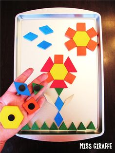 Awesome trick! Stick magnets to the back of pattern blocks so kids can use a magnetic cookie sheet to create pictures that stay put in their laps - great for long car rides too!