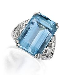 PLATINUM, AQUAMARINE AND DIAMOND RING. Set with an emerald-cut aquamarine weighing approximately 18.05 carats, flanked by square-cut and baguette diamonds weighing approximately 1.00 carat