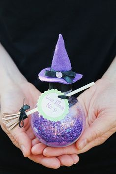 "Love Potion No. 9 Witches Cauldron Materials: Mini plastic jars (found at Hobby Lobby) purple Martha Stewart glitter Black satin ribbon Purple felt Decorative gems ""Love Potion No. 9"" tag (.50 cents Icing Designs) Lollipop stick Strip of brown card stock Hot glue gun/glue For more info: icingdesignsonline.blogspot.com Etsy icingdesigns"