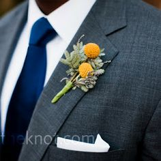 A billy ball boutonniere looks great with this groom's gray suit