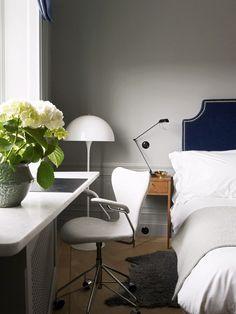 Velvet headboard with a modern lamp and desk.