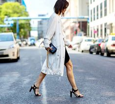 A black dress is worn with a white trench coat, black sandals, and a Saint Laurent bag