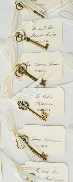 "creative escort card idea: antique brass skeleton keys tied with ivory ribbon and cards with guests names and table numbers + gold picture frame sign with message ""you may find your seat here, but your presence on the dance floor is key!"""