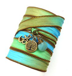 Take a breath with calming amazonite!  This silk wrap bracelet features an antique brass Om charm, tree of life, and a genuine wire wrapped amazonite briolette on a hand painted silk ribbon.  It is 42 inches long - Just wrap around your wrist several times, tie, tuck in the ends, and you are ready to go! This wrap also makes a great anklet or necklace, so you are really getting three pieces of jewelry in one.