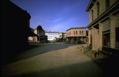 """Behind the cowtown street on Paramount's Hollywood lot, a fake sunny blue sky rises unruffled by wind or rain or dark of night."""