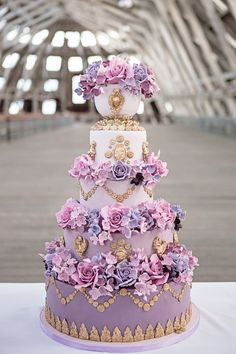Marie Antoinette Wedding Cake - A purple ombre Marie Antoinette wedding cake decorated with large roses, gold cherubs and gold swags.