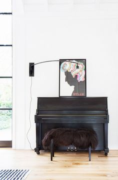 Bright living space with a black piano, a lamb sham bench and colorful art