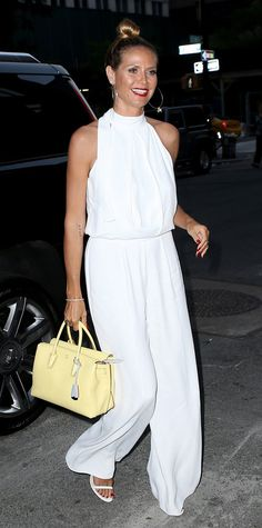 Heidi Klum perfected her summer uniform when she was snapped stepping out in an all-white look, featuring a halter top with breezy wide-leg pants and sandals. The finishing touches? A cherry-red lip and a lemon-yellow MCM top-handle purse for a nice dose of color.