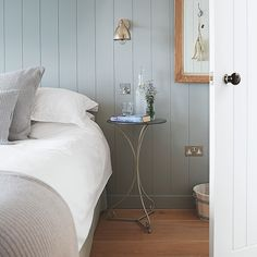 Bedroom with grey panelled walls, wall light and small circular table Opt for a restricted colour palette, giving a small bedroom a calm look with panelled walls painted in grey, crisp white bedlinen and cosy ribbed cushions. The wall-mounted light frees up space on the table for some bedtime reading.  #Sleeptember