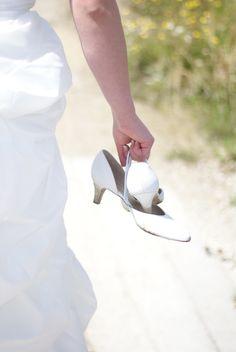 De trouwschoenen even uit om op het strand van Netl parc tijdens de huwelijksfotografie de ultieme trouw foto's te maken. De bruid had haar schitterende trouwjurk iets opgetrokken en dat leverde mooie foto's op. Hartelief Huwelijksfotografie met oog voor detail.