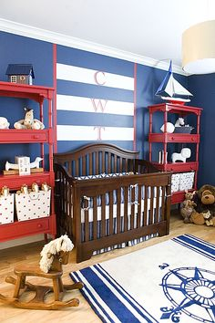 Navy blue and white theme pair with red bookshelves in this nursery, featuring dark stained wood crib over lighter natural wood flooring. Compass rug in blue and white completes the theme.
