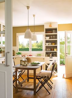 Kitchen in a house in Spain - French bistro chairs, gold walls, white cabinets, white Corian counters