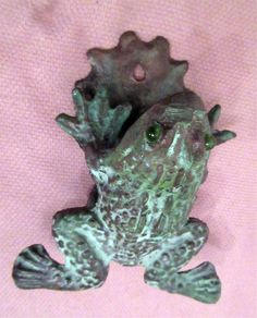 Antique bronze and glass frog front door knocker made of thick bronze and has acquire a lovely patina from age. The eyes are made from a vibrant green glass. It pivots back and forth on a back hinge connected to the thick bronze backplate. Made in Mexico, measures 4 1/2 inches by 3 3/4 inches and is in nice condition.