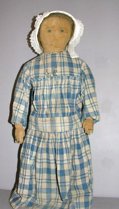"PRIMITIVE CLOTH DOLL, 29"". Hand sewn cotton stuffed body has head attached at chest level, gusseted shoulders, individual fingers with ring. Worn facial painting includes blue eyes, brows, nose and mouth and wig is blond human hair. Blue checked dress is mostly hand sewn, bonnet. Age stains and wear, water marks on legs, face is darkened with some water spots."