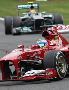 Mercedes AMG driver Lewis Hamilton of Britain, background, chases Ferrari driver Fernando Alonso of Spain during the Belgian Formula One Grand Prix in Spa-Francorchamps, Belgium