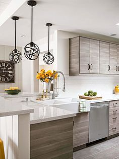 Modern gray kitchen with apron-front double-bowl sink and restaurant-style pull-down faucet.
