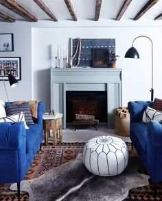 Cozy living space with exposed ceiling beams, a painted fireplace, matching blue sofas, and layered rugs (via @mydomaine)