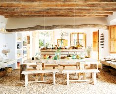 An earthy and rustic dining space with incredible stone floors, wood benches, and wood table