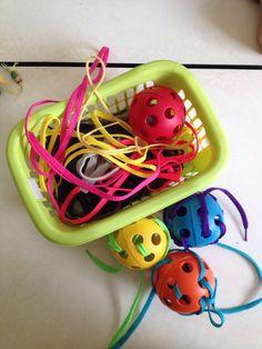 Met veters rijgen door balletjes (speelgoed van honden) Fijne motoriek!