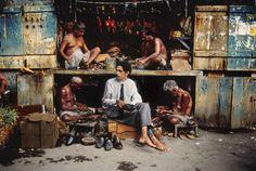 Steve McCurry -   At the shoemaker, Mumbai (Bombay), India, 1996.