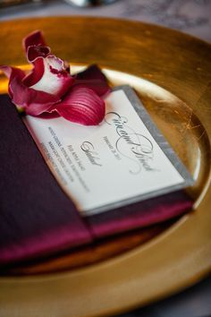 Dark burgundy orchid on menu wrapped with maroon napkin on gold charger plate dark and moody decor ideas