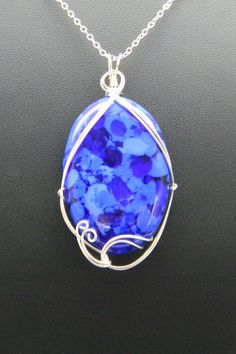This is a handcrafted fuzed blue glass cabochon created by Jewelry by Christabel (http://jewelrybychristabel.com/). It is wrapped in sterling silver and hangs from a sterling silver chain. $65.00